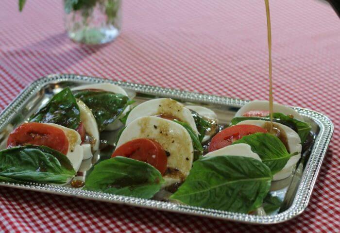 drizzle the tomato mozzarella caprese salad with balsamic vinaigrette