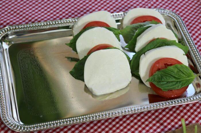 layer the ingredients for tomato mozzarella caprese salad