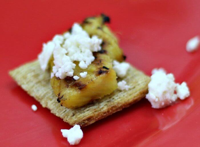 Add feta cheese to the top of the pineapple on the cracker