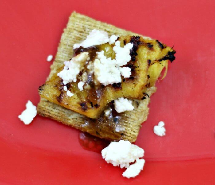 Drizzle the cracker and toppings with balsamic glaze