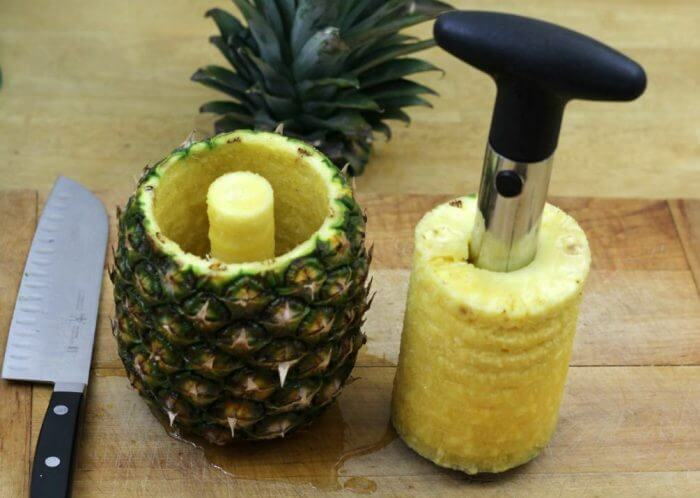 Pull the corer and the center out of the pineapple