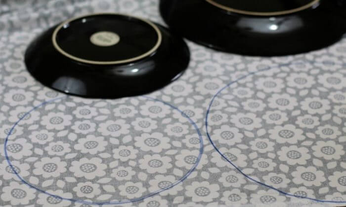Trace circles on the back of the laminate fabric. You need two circles for each cover you want to make.